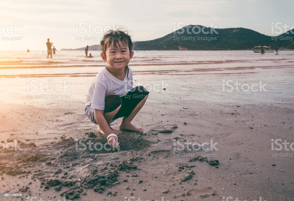 Happy asian child has fun digging in the sand. Travel on vacation. royalty-free stock photo