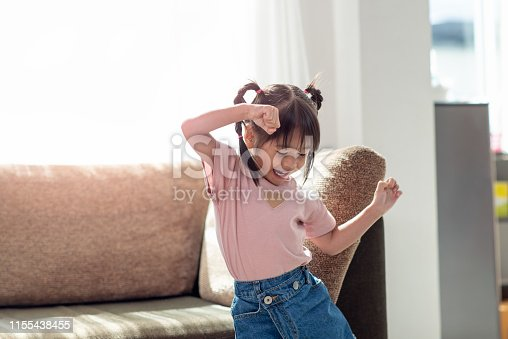 Happy Asian child having fun and dancing in a room, active leisure and lifestyle concept