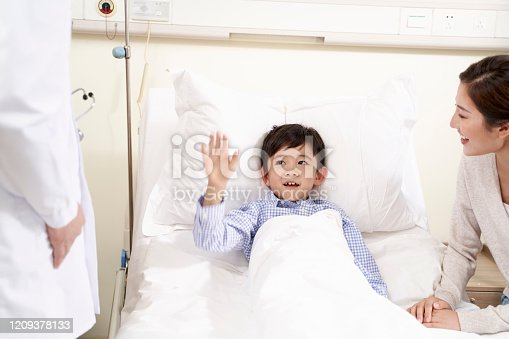happy five year old asian kid lying in bed in hospital ward waving good-bye to doctor