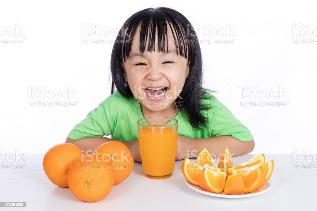 Happy Asian Chinese little girl drinking orange juice royalty-free stock photo