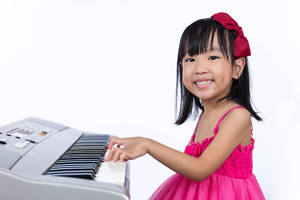 Happy Asian Chinese little girl playing electric piano keyboard Asian Chinese little girl playing electric piano keyboard in isolated white background. keyboard player stock pictures, royalty-free photos & images