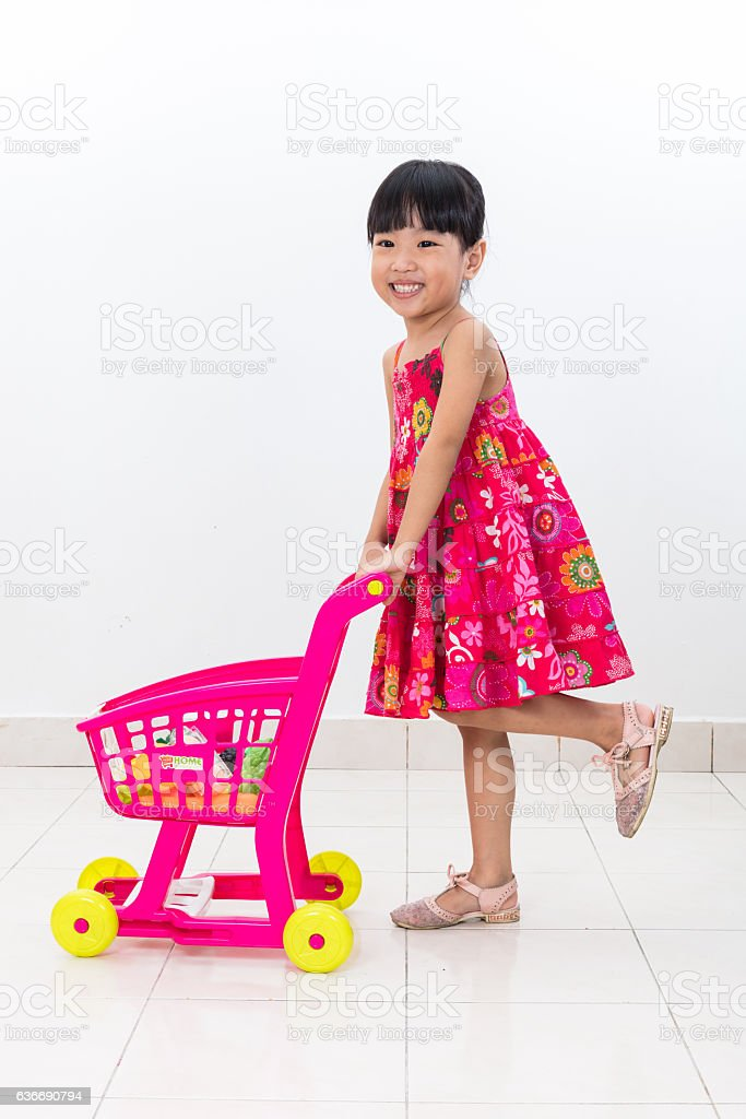 Happy Asian Chinese little girl pushing toy trolley - foto stock
