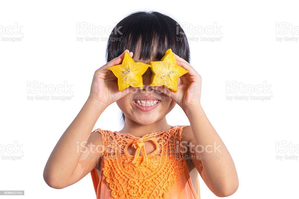 Happy Asian Chinese little girl using starfruit as glasses stock photo