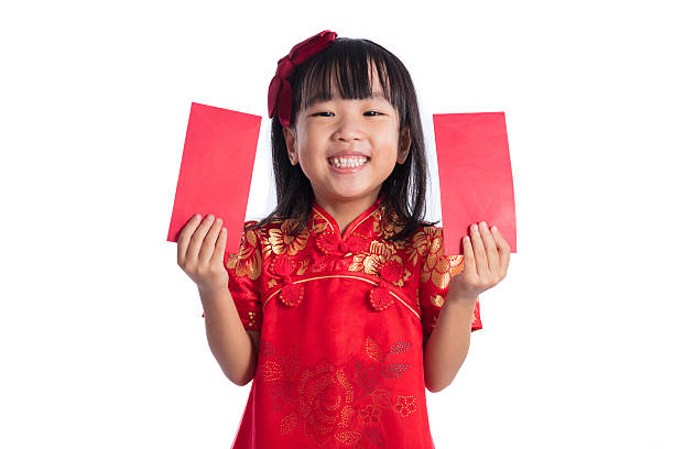 happy asian chinese little wearing cheongsam and holding red env - kinder verpackung stock-fotos und bilder