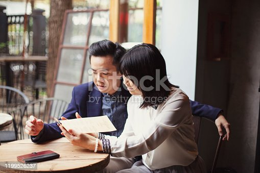 Happy Asian couple having lunch at a restaurant and looking at the menu