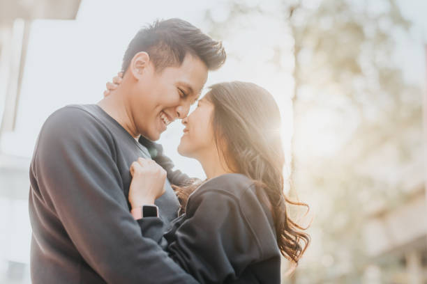Happy Asian couple in love embracing outdoor stock photo