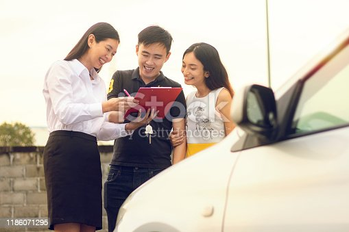 939005154 istock photo Happy Asian Couple purchasing and signing sales contract for car at dealership 1186071295