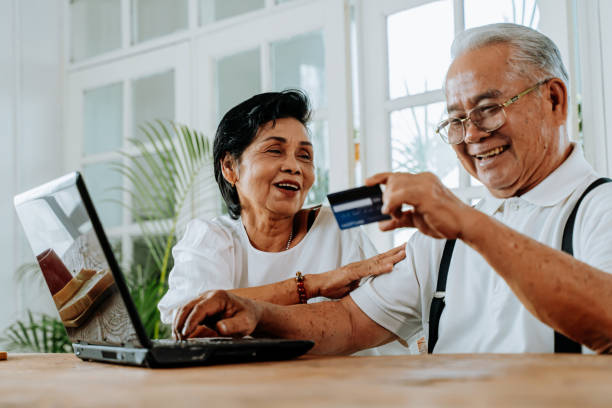 Happy Asian couple shopping online together stock photo