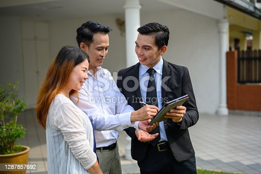 Happy Asian couple signing contract agreement with digital tablet from real estate agent in front of their new house. Concept for real estate, moving home or renting property.
