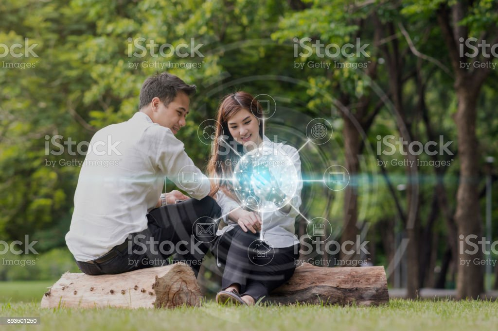 Happy asian couple using and listening the song and using the social network via smart mobile phone for online shopping with omni channel in the park, lifestyle and technology concept stock photo