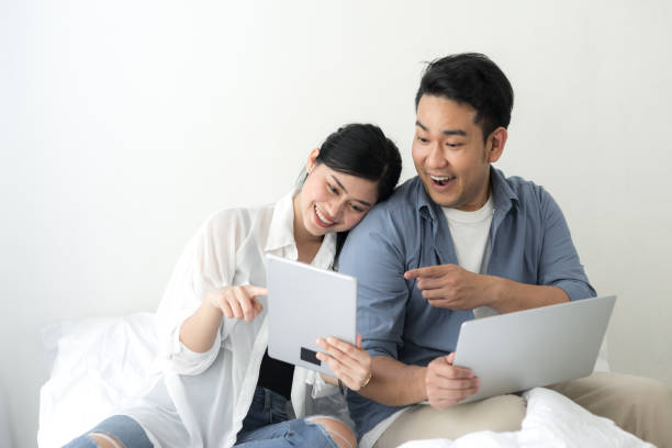 Happy Asian couple using laptop at home, lifestyle concept. Happy Asian couple using laptop at home, lifestyle concept. shopping couple asian stock pictures, royalty-free photos & images