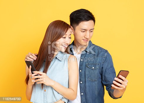 Happy Asian couple watching the smartphone
