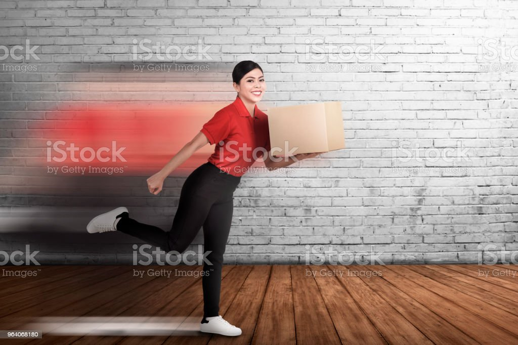 Happy asian courier woman delivering the package - Royalty-free Adult Stock Photo
