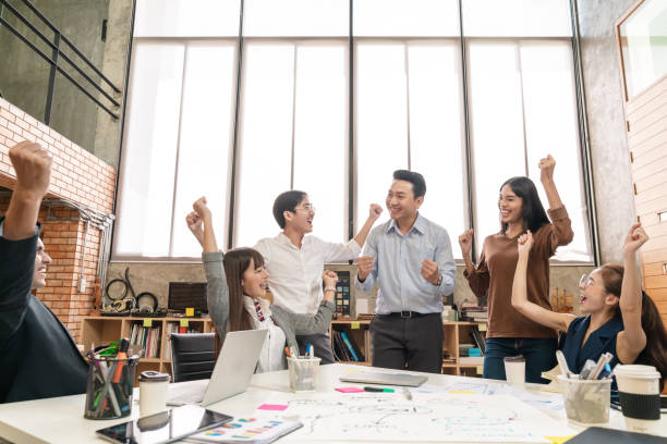 Happy asian creative team or staff employee feeling enjoy and looking together in meeting room at modern office. Brainstorming and planning to achieve goal with smart work. stock photo