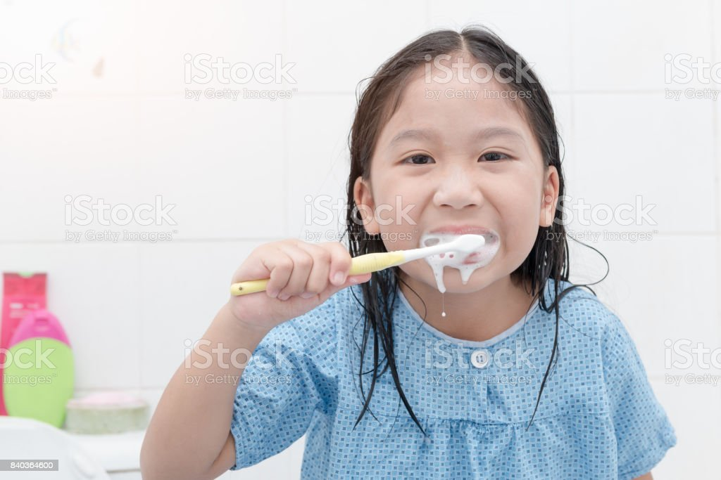happy asian cute girl brushing teeth in bathroon stock photo