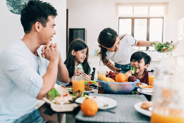 Happy Asian ethnicity family at the table stock photo