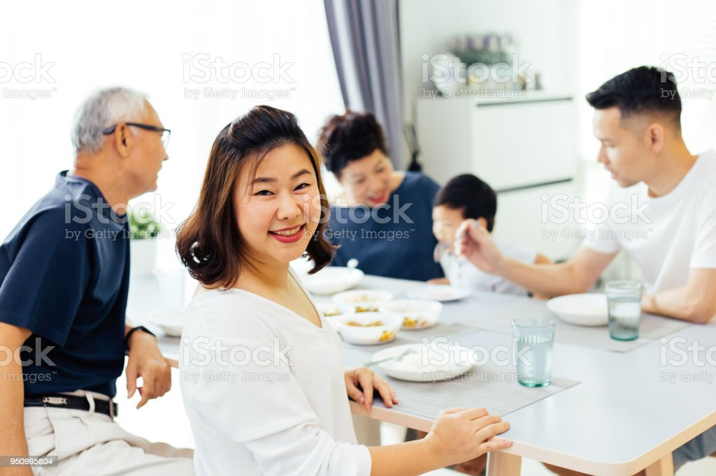 Happy Asian extended family having dinner at home full of happiness and smiles stock photo