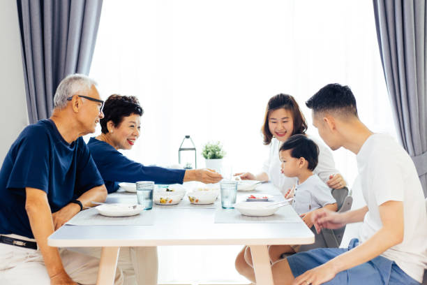Happy Asian extended family having dinner at home full of laughter and happiness stock photo