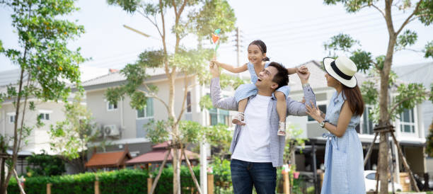 Happy Asian family. Father gave his daughter a piggyback at a park at natural sunlight background and house. Family vacation concept with copy space stock photo