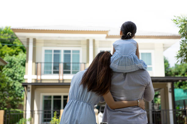 Happy Asian family. Father, mother and daughter near new home. Real estate background with copy space stock photo
