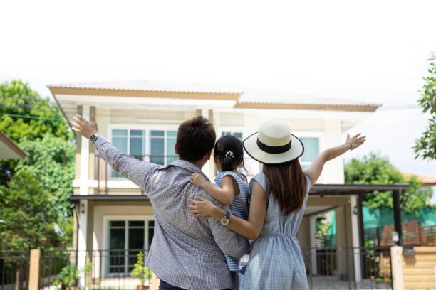 Feliz familia asiática. Padre, madre e hija cerca de un nuevo hogar. Fondo inmobiliario con espacio de copia - foto de stock