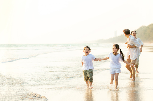 Asian grandparents with grandchildren running and having fun together on the beach