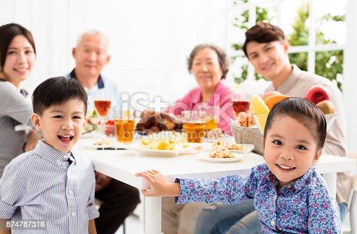 istock happy asian family having dinnerat home 874787316
