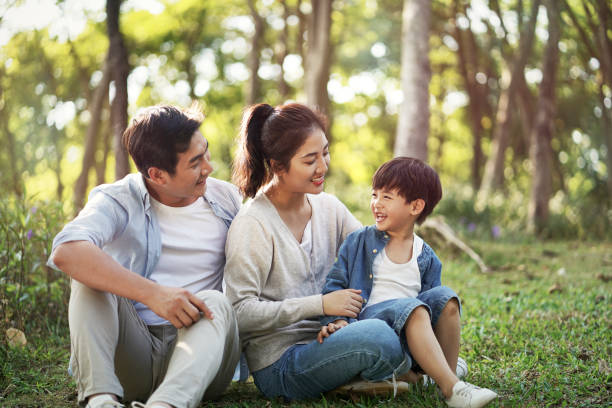happy asian family having fun in woods stock photo