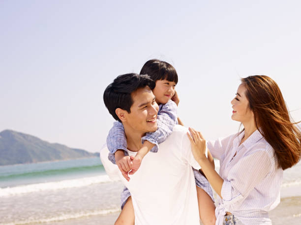 happy asian family having fun on beach stock photo