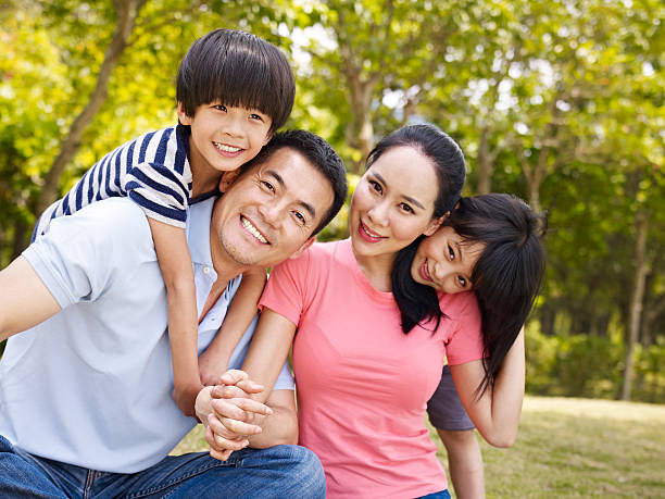 happy asian family in park - east asian ethnicity stock photos and pictures