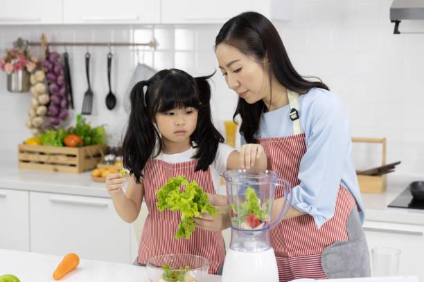 Feliz familia asiática en la cocina. Madre y niña están preparando la ensalada en licuadora Menú sabroso batido e ingredientes en la mesa en casa. Cocinar alimentos, concepto de comida saludable - foto de stock