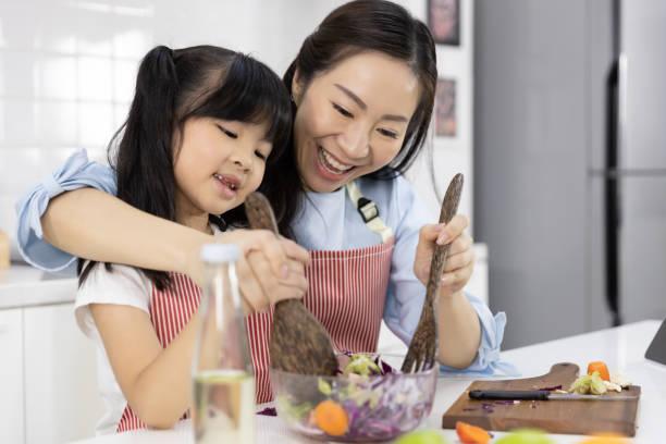 Feliz familia asiática en la cocina. Madre y niña están preparando la ensalada en tazón e ingredientes en la mesa en casa. Concepto de cocina de alimentos, alimentos saludables y cuidado de la salud - foto de stock