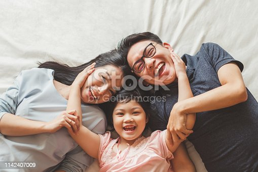 istock Happy Asian family laying on bed in bedroom with happy and smile, top view 1142407009