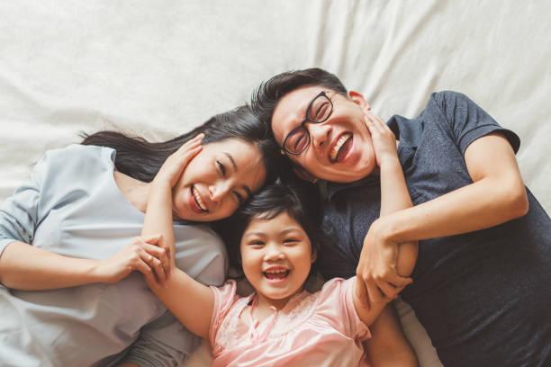 快樂的亞洲家庭躺在床上的臥室與快樂和微笑, 頂視圖 - 亞洲 個照片及圖片檔