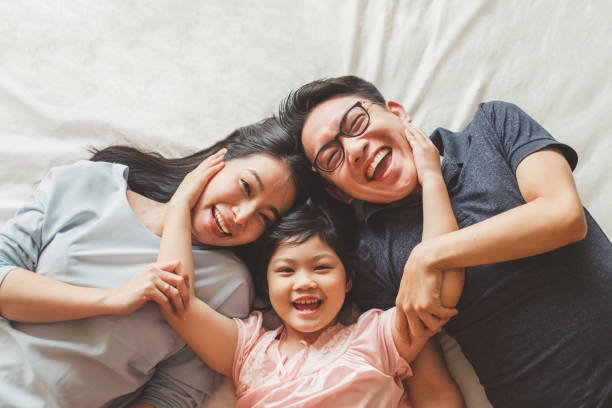happy asian family laying on bed in bedroom with happy and smile, top view - generazioni foto e immagini stock
