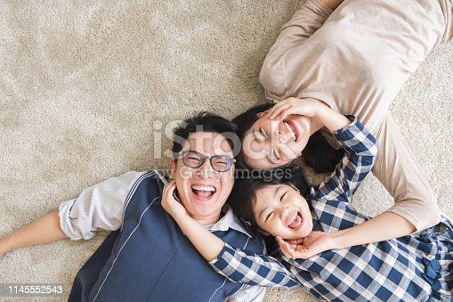 Happy Asian family laying with happy and smile, top view