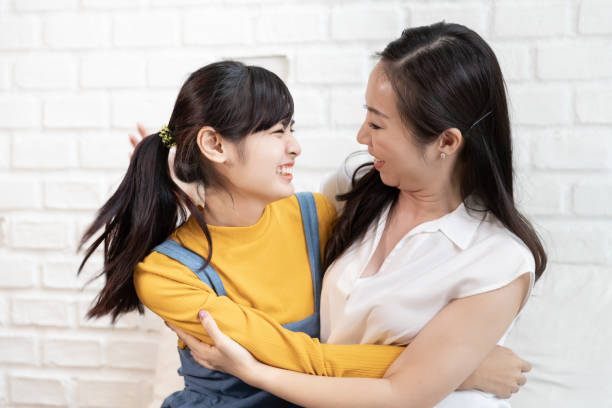 Happy Asian family Mom and teenage daughter embrace together excited, glad in a room that has sunlight from the window at home. Show Love family concept stock photo