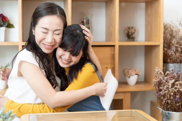 Feliz familia asiática Mamá y adolescente hija abrazar juntos en una habitación con la luz del sol de la naturaleza en casa. Mostrar el amor, el concepto del Día de la Madre Feliz - foto de stock
