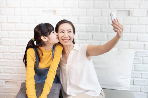 Feliz familia asiática mamá y adolescente hija Tome una foto de sí mismo, Selfie o videollamada con teléfono inteligente en una habitación con luz solar de la naturaleza en casa. - foto de stock