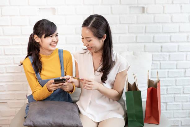Feliz familia asiática mamá y adolescente hija usando teléfono inteligente compras en línea con tarjeta de crédito en una habitación con luz solar de la naturaleza en la casa. Concepto de compras en casa - foto de stock