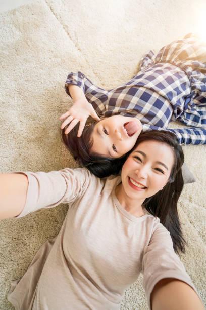 Glückliche asiatische Familie Mutter und Tochter, die ein Selfie-Foto, während der Verwendung in Wohnzimmer zu Hause Hintergrund. – Foto