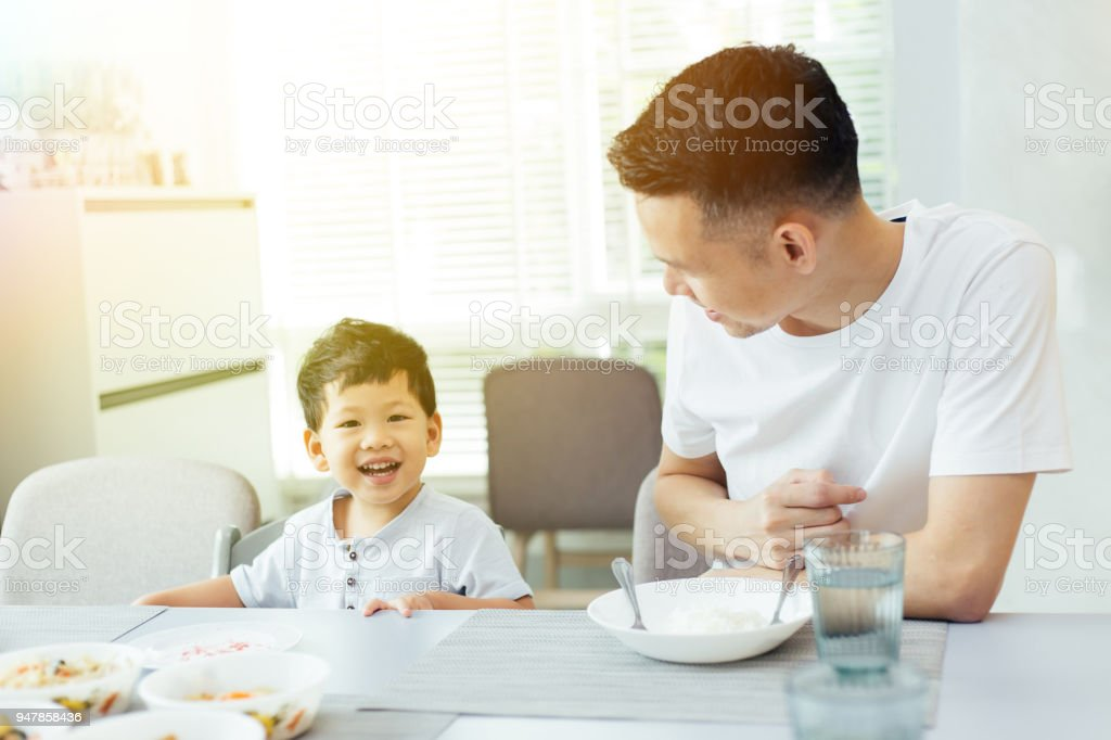 Happy Asian family of father and son playing and laughing while having dinner stock photo