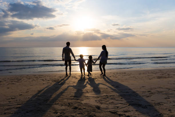 Happy Asian Family On Summer Vacation Father, mother, son and daughter holding hands Running down to the seashore together. Background sunset in sea. Relax Holiday and Travel concept. stock photo