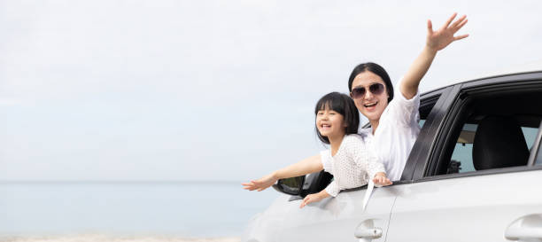 Happy Asian Family On Summer Vacation Mother and daughter Open arms playing plane flying together in car on the beach. Holiday and Car Travel concept. panoramic web banner with copy space stock photo