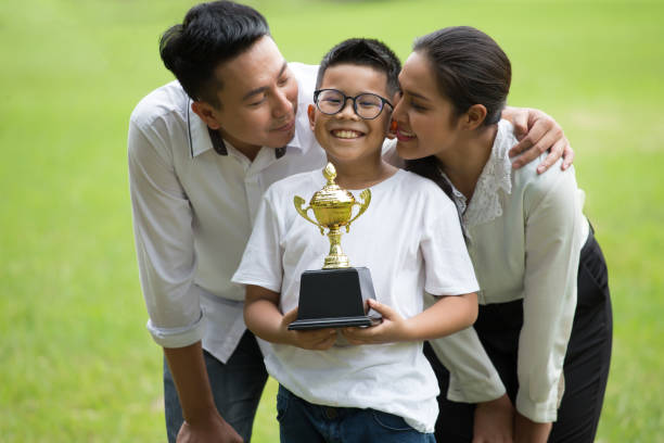 happy asian Family, parents and their children holding trophy  in park together. father and mother embracing and kiss son celebrate of achievement ,successful,winning ,kid,enjoy,Congratulation stock photo