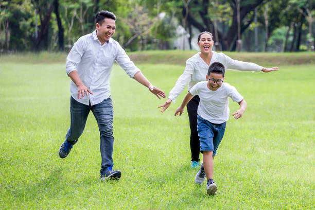 happy asian Family, parents and their children running around  in park together. father mother and son having fun and laughing outdoors . cheerful stock photo