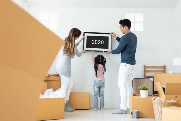 Feliz imagen de la familia asiática sosteniendo marco durante la mudanza de la casa juntos. - foto de stock