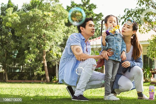Happy Asian family playing in garden blowing bubble, happy and smile