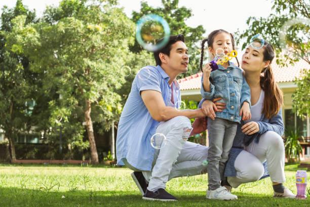 快樂的亞洲家庭在花園裡玩吹泡泡, 快樂和微笑 - 亞洲 個照片及圖片檔