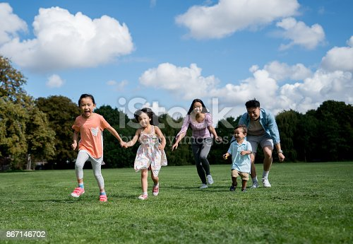 589135214 istock photo Happy Asian family running at the park 867146702